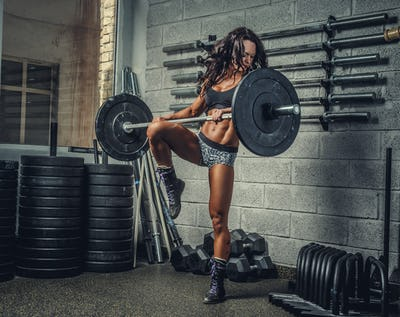 Female with barbell in a gym club.