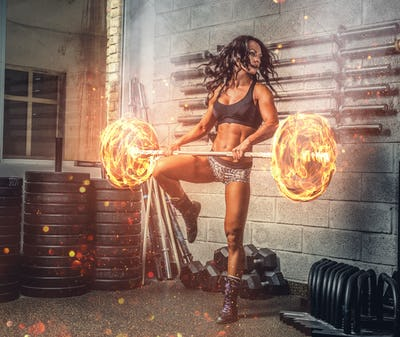 Brunette fitness woman exercising with burning barbell.