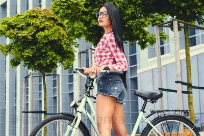 Female posing on a bicycle over modern building background.