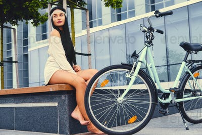 Female sits on a bench over modern building background after bicycle ride.