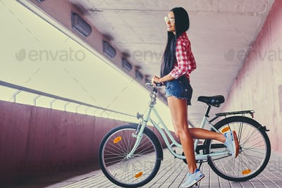 A woman posing on a bicycle in a tunnel with pink walls.