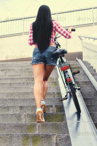 A woman taking her bicycle up on a bridge.