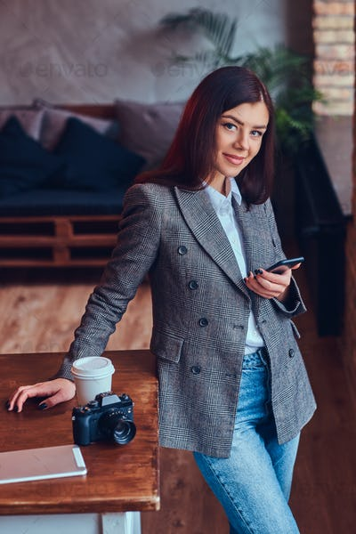 Portrait of a young female photographer works with a phone leani