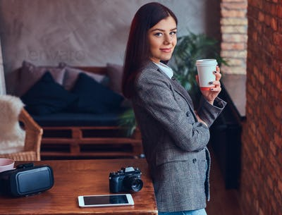 Portrait of a young female photographer holds a cup of a morning