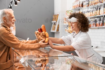 Female butcher giving sausages to eldery man