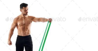 Shirtless bodybuilder using resistance band