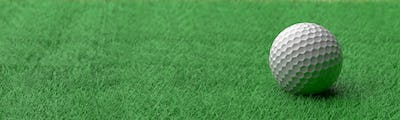 White golf ball on green grass golf course, close up view. 3d illustration