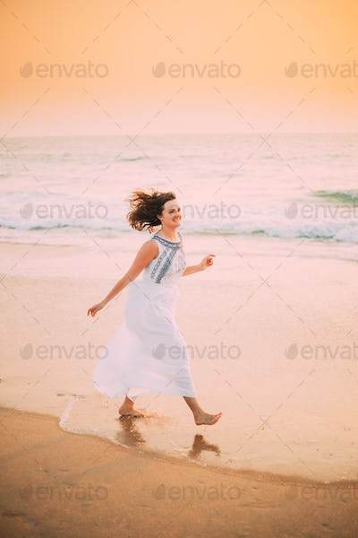 Goa, India. Young Caucasian Woman With Fluttering Hair In Wind In White Dress Walking Along Seashore
