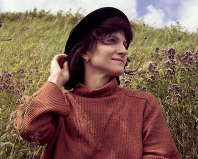 Portrait of adult female in hat sitting in meadow Karelia