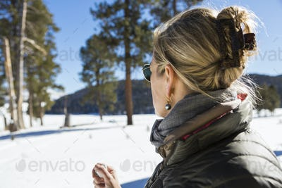 A woman looking at a beautiful snow landscape with pine trees.