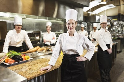 A portrait of a caucasian female chef and her team of chefs in the backgroiund.