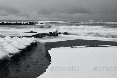 Snow-covered wave breakers near an inlet in winter.