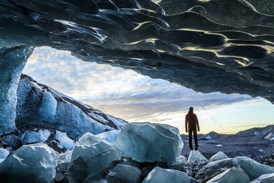Rear view silhouette of person standing on ice rock at the entrance to a glacial ice cave.