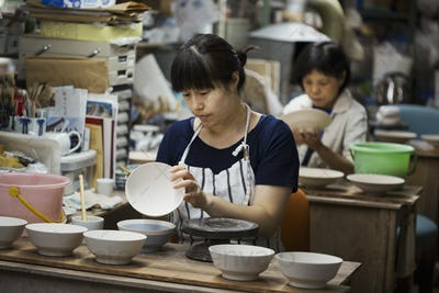 Two women sitting in a workshop, working on Japanese porcelain bowls.