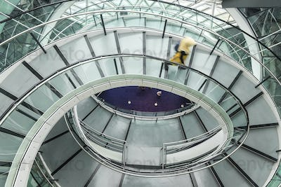 Interior view of building with person walking along glass and metal spiral staircase.