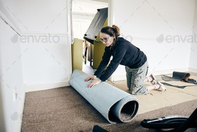 Woman rolling up old carpet in preparation to renew flooring