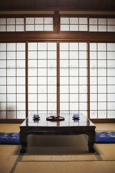 Traditional Japanese interior with low table set with bowls of tea.