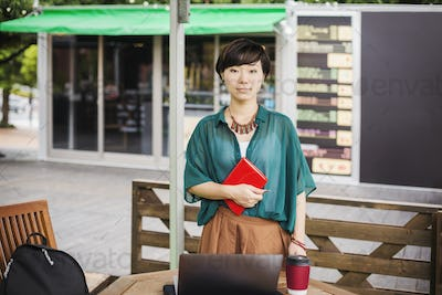 Woman with black hair wearing green shirt standing outdoors at a street cafe, looking at camera.