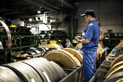 Japanese man wearing baseball cap and blue overall standing in factory, working.