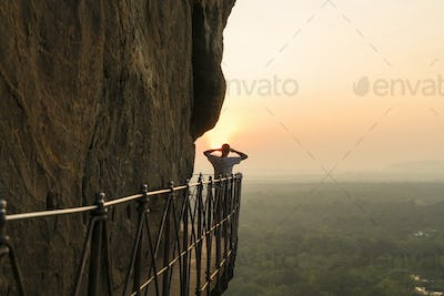 Rear view of man standing on narrow walkway on steep rock, admiring landscape view at sunset.