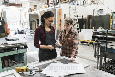 Two women standing at workbench in metal workshop, holding digital tablet.