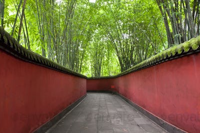 View along walkway with red walls through bamboo forest.
