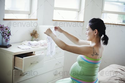 A pregnant woman in a baby's nursery room, folding baby clothes.