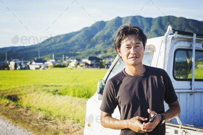 A man standing by a truck in an open landscape with rice paddies behind him, holding a mobile phone.