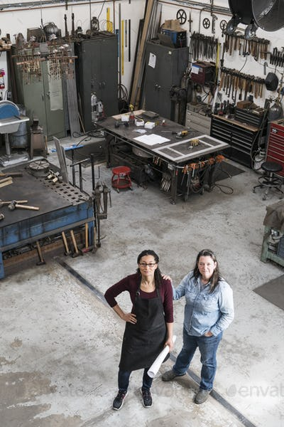 High angle view of two women standing in metal workshop, looking at camera.