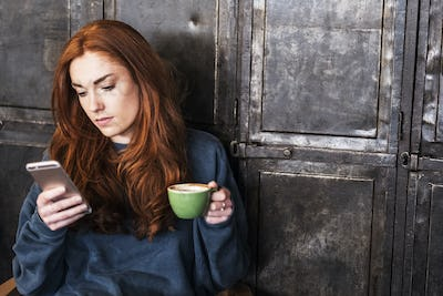 Young woman with long red hair sitting at table, holding cup of coffee, checking her mobile phone.