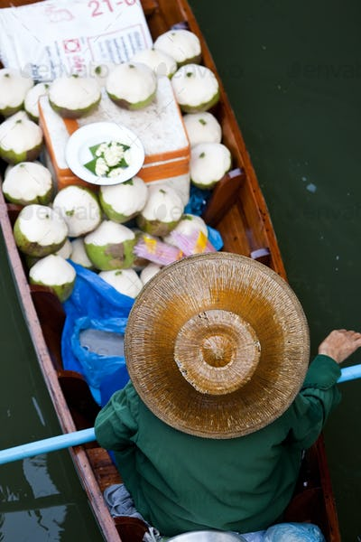High angle view of person wearing hat sitting in narrow boat, transporting green coconuts.