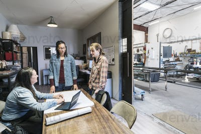 Three women gathered around table in office area of a metal workshop.