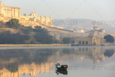 Fisherman in boat on calm lake at sunrise, large fort on hill in the distance.