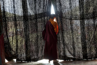 Rear view of young monk wearing red robe looking through black curtains at a monastery.