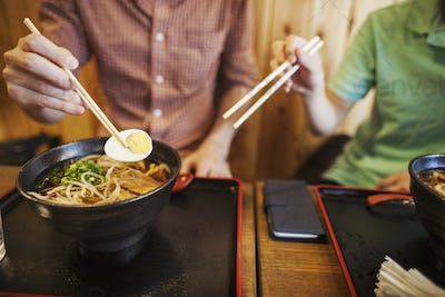 Two people, a Japanese man showing a Western man how to use chopsticks in a noodle shop.