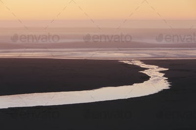 Landscape with small stream flowing into surf at dusk.