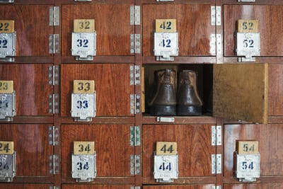 One pair of shoes in a shoe locker with an open door. Lockers in a row, with numbers.