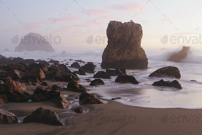 Seascape with breaking waves on rocks on sandy beach at dusk.