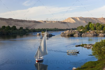 High angle view of sailboats on a river, sand hills in the distance.