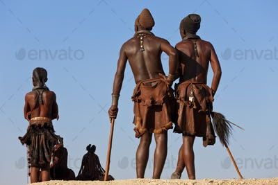 Small group of Himba men wearing traditional clothing standing in a desert.
