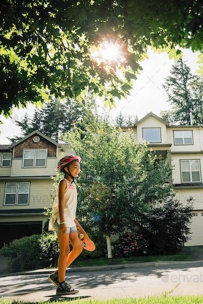 Tween Girl Walking on Sidewalk Carrying Skateboard in Residential Neighborhood