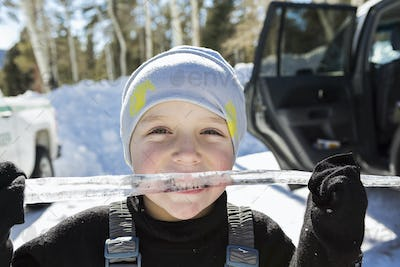 Smiling six year old boy with a long icicle in his mouth