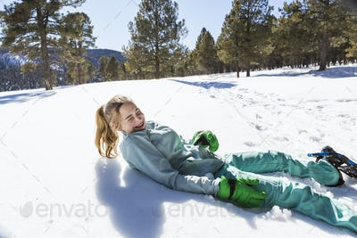 A teenage girl wearing snow shoes lying in the snow laughing
