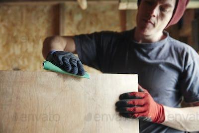 Carpenter sanding down wood