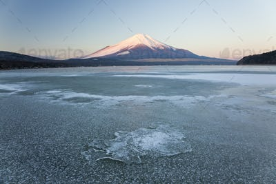 Ice on Lake Yamanaka with snow covered Mount Fuji in background, Japan.