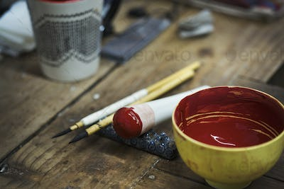 Close up materials in a Japanese porcelain workshop, bowl with red paint, pestle and paintbrushes.