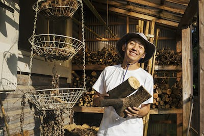 Smiling man wearing hat standing outdoors, wearing hat, holding logs of firewood, looking at camera.