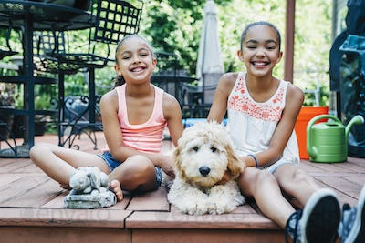 Mixed Race Sisters Play with Labradoodle Puppy on Porch
