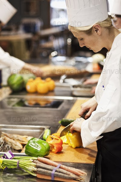 A caucasian female chef works cutting vegetables in a commercial kitchen,
