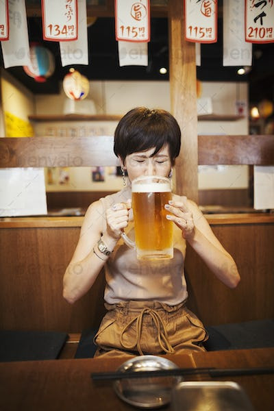 Woman sitting at a table in a restaurant, drinking from large glass of beer.